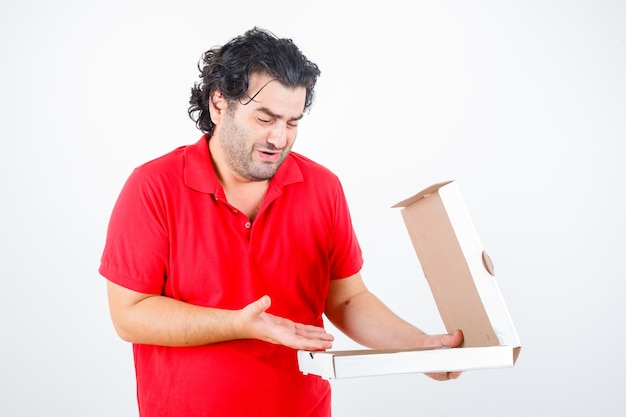 Handsome man opening paper box, stretching hand toward it with dismal manner in red t-shirt and looking disappointed , front view.