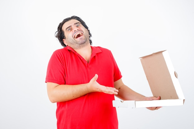 Handsome man opening paper box, stretching hand toward it with happy manner in red t-shirt and looking jolly. front view.