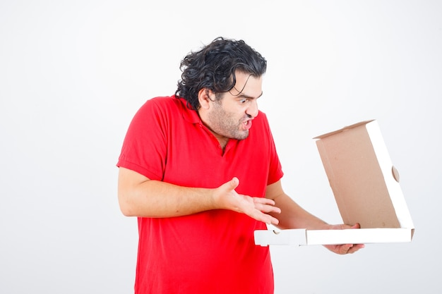 Handsome man opening paper box, stretching hand toward it with surprised manner in red t-shirt and looking shocked , front view.