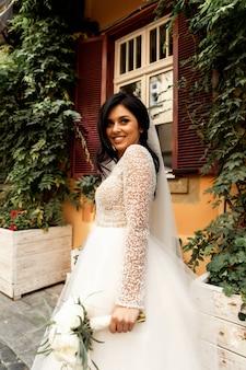 ハンサムな男やアフリカ系アメリカ人の新郎が街の街背景をぼかした写真の屋外の白いセクシーなウェディングドレスで美しいブロンドの髪のかわいい女の子やかわいい花嫁を抱いて