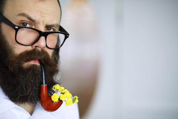 Красивый мужчина или лесоруб, бородатый хипстер, с бородой и усами в рубашке с курительной трубкой