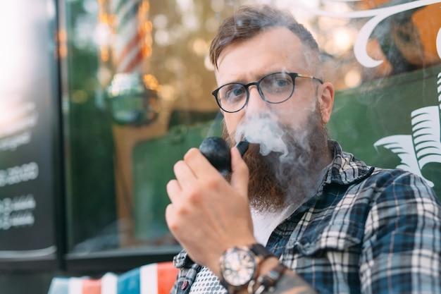 ハンサムな男または木こり、ひげを生やしたヒップスター、ひげと口ひげの喫煙パイプ。