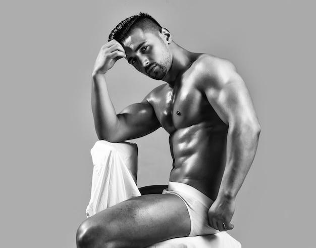 흰색 속옷에 기름진 피부가있는 6 팩과 복근 삼두근 팔뚝이있는 섹시한 근육 몸통 몸매를 가진 잘 생긴 남자 또는 근육질 보디가 회색 의자에 앉아있다.