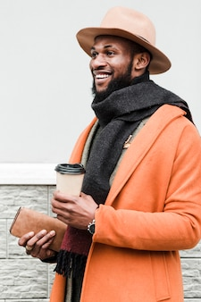 Handsome man in orange coat holding his coffee and his wallet
