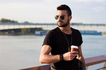 Handsome man outdoors drinking coffee. With sunglasses, a guy with beard. Instagram effect.