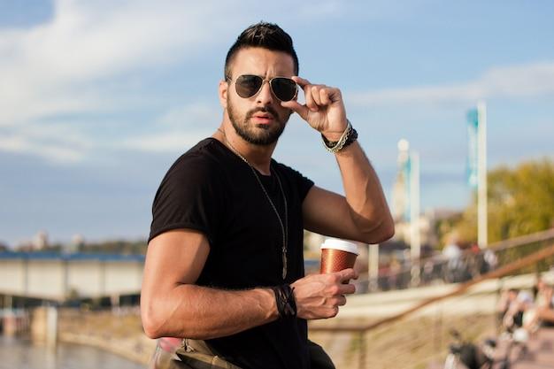Красивый человек на открытом воздухе, пить кофе. с солнечными очками, парень с бородой. эффект instagram.