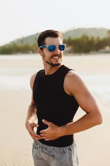 해변에서 잘 생긴 남자 야외 초상화입니다. 검은 색 민소매 티셔츠와 반바지를 입고 있습니다. 바다 근처의 따뜻한 태양 날씨
