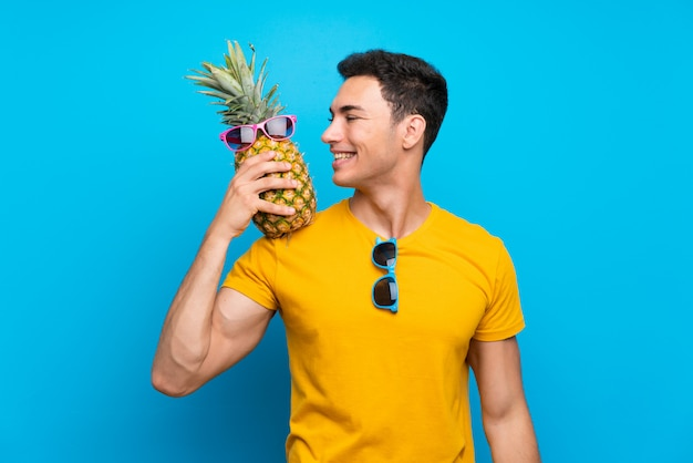 Красивый мужчина на синем фоне, держа ананас с sunglasse