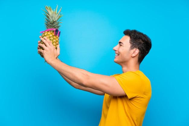 Красивый мужчина над синей стеной, держа ананас с sunglasse