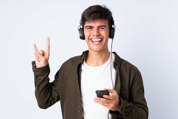 Красивый мужчина над синей стеной прослушивания музыки с мобильного телефона, делая рок жест