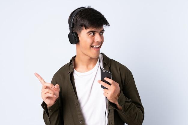 Красивый мужчина на синем фоне прослушивания музыки с мобильного телефона и пения