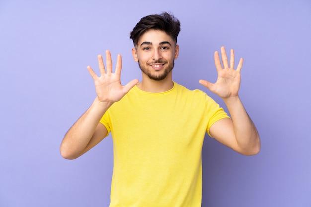 Красивый мужчина на изолированной стене, считая десять с пальцами