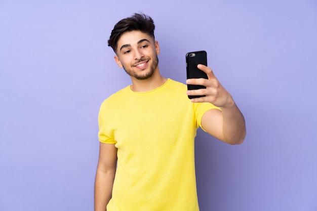 Selfieを作る孤立した壁の上のハンサムな男