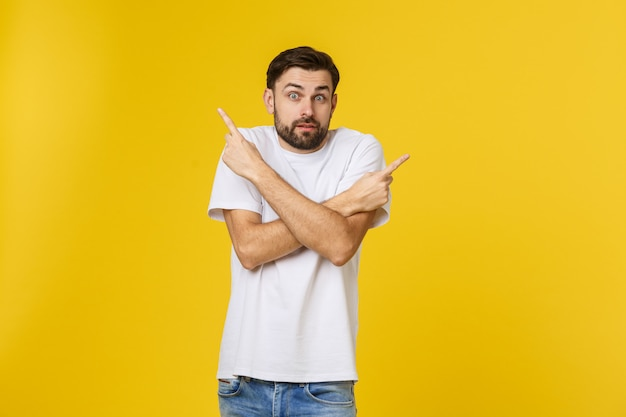 Красивый человек над изолированной желтой стеной разочарованный и указывая к фронту.