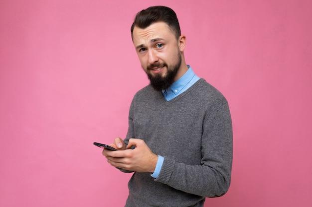 Красивый мужчина на розовом фоне, отправив сообщение с мобильного телефона
