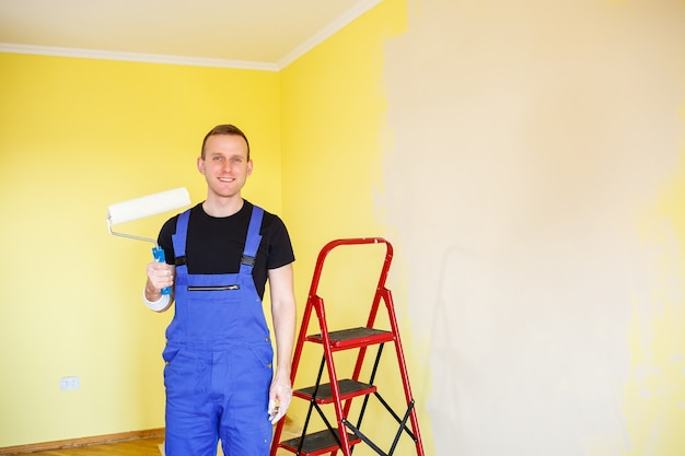 Handsome man in overalls hold paint roller,. tools accessories for apartment room renovation. home renovation concept