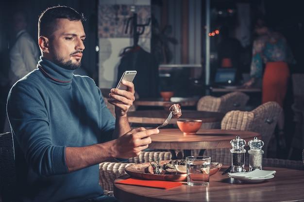 Красивый мужчина фотографирует еду в ресторане