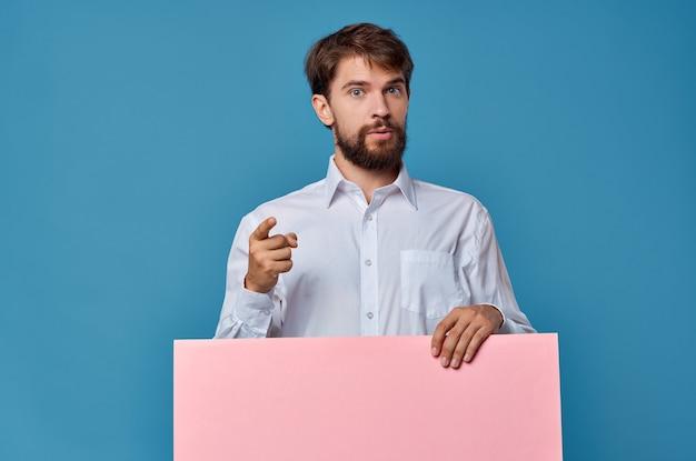マーケティングの楽しいライフスタイルの青い背景の手にハンサムな男のピンクの紙