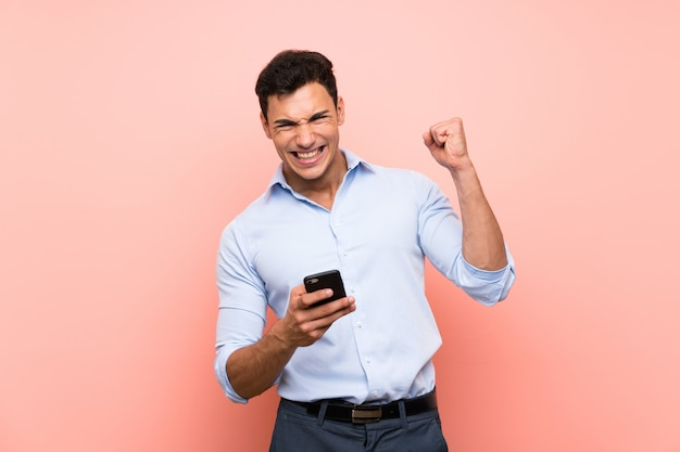 Handsome man over pink  with phone in victory position