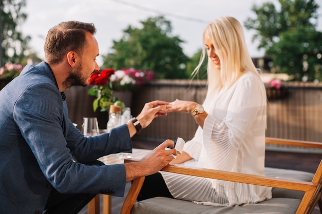 Handsome man placing wedding ring on blonde woman's hand in the restaurant