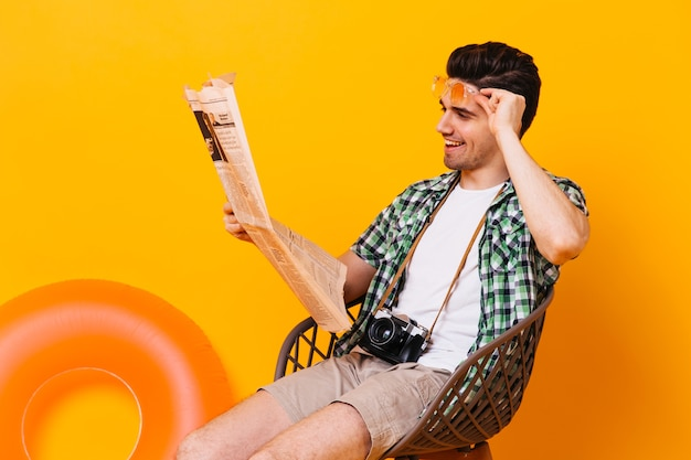 Handsome man in plaid shirt and shorts is sitting, reading newspaper and resting on orange space with inflatable circle.