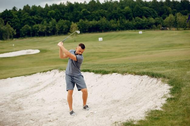 ゴルフコースでゴルフをするハンサムな男