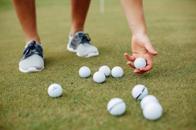 Красивый мужчина играет в гольф на поле для гольфа