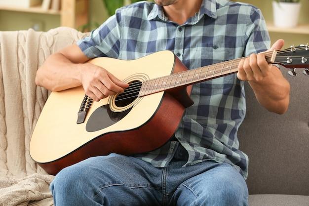 家でギターを弾くハンサムな男