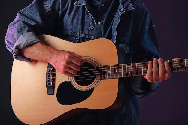 Красивый мужчина играет на гитаре в темноте