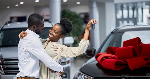 Handsome man pleases his wife in dealership