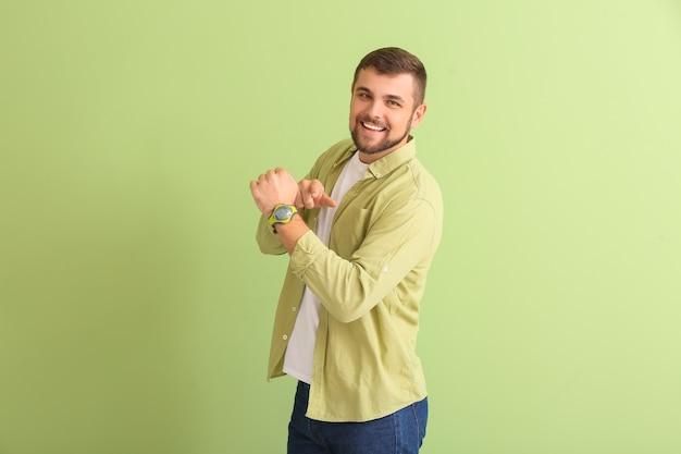 Красивый мужчина, указывая на наручные часы на зеленом