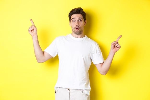 黄色の背景の上に立って、2つのプロモーションを示して、指を横向きに指しているハンサムな男