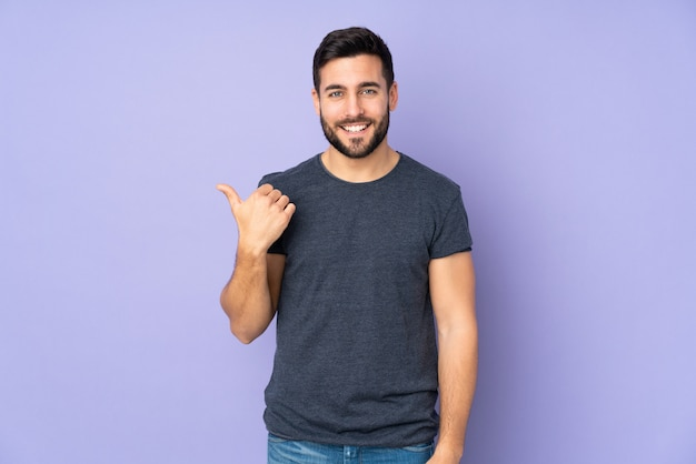 Handsome man pointing to the side to present a product over purple