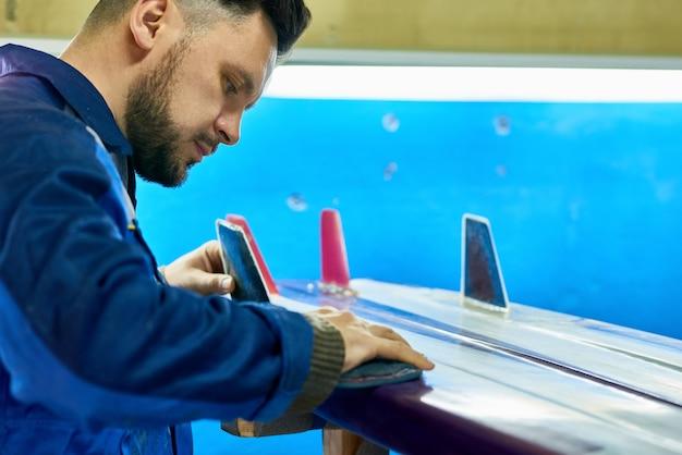 Handsome man polishing cistom surfing board  in workshop