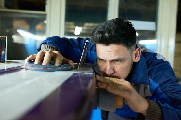 Handsome man polishing surfing board in workshop