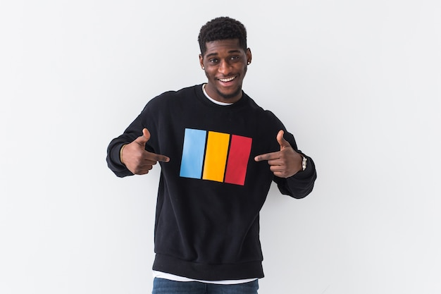 Handsome man posing in black sweatshirt on a white wall