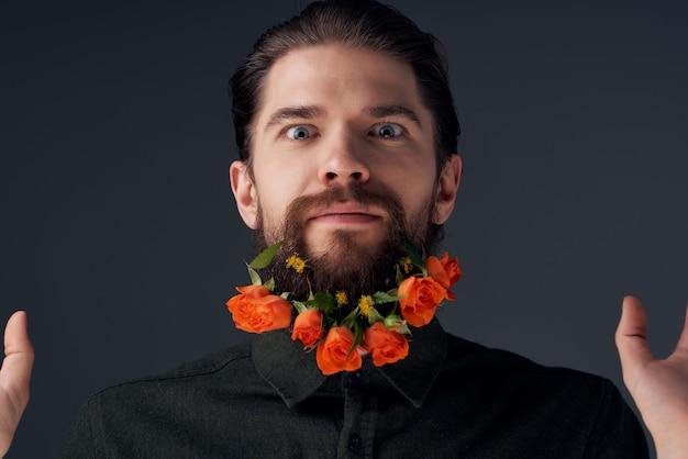 ひげのファッションの孤立した背景で花をポーズするハンサムな男。高品質の写真