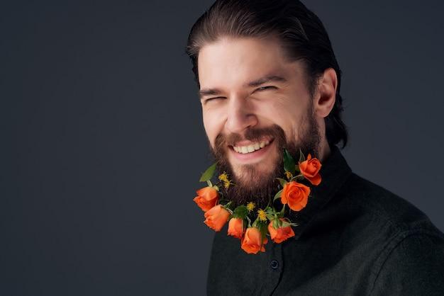 ひげのファッションの孤立した背景で花をポーズするハンサムな男