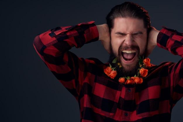 ひげのファッションライフスタイルの暗い背景で花をポーズするハンサムな男