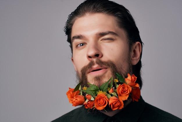 ひげのファッションスタジオライフスタイルで花をポーズするハンサムな男。高品質の写真