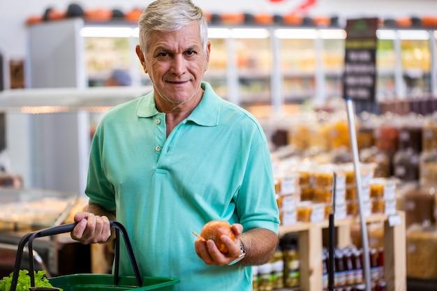 ポーズをとって、見て、果物を手に持っているハンサムな男。ひげを生やした顧客の笑顔。スペースに新鮮な柑橘類のセクション。