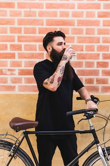 Handsome man posing near his cycle against wall
