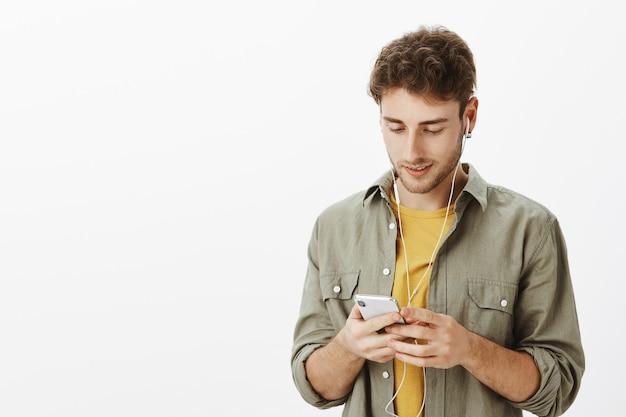 スタジオでスマートフォンでポーズをとるハンサムな男