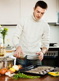 Красивый мужчина, наливая масло в сырую рыбу на поджаривание