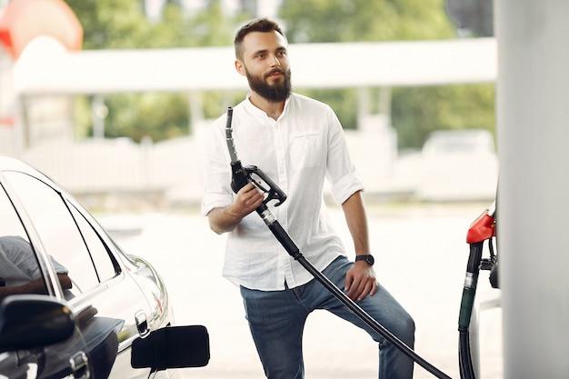 ハンサムな男は車のタンクにガソリンを注ぐ