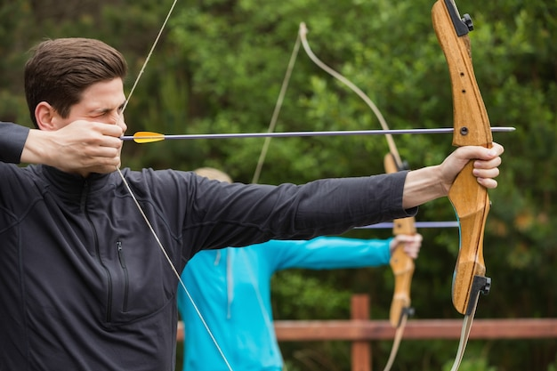 Handsome man practicing archery