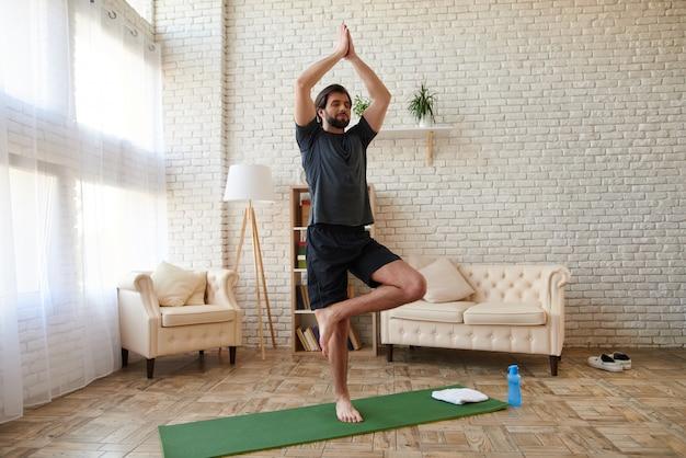 Handsome man practicing yoga, folding hands together.