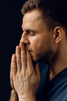 잘 생긴 남자는기도하고 하나님을 믿습니다. 정통 기독교 신앙. 남자는 손으로 얼굴을 가리고 삶에 대해 생각합니다.