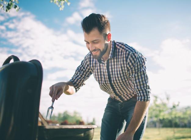 友人のためにバーベキューを準備するハンサムな男。バーベキュー-屋外の公園でグリルにいくつかのソーセージとペパロニを入れてシェフ-夏の間に屋外で食べることの肉を調理する男。
