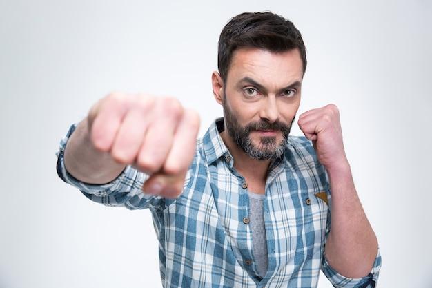 Красивый мужчина пробивает кулаком, изолированным на белой стене